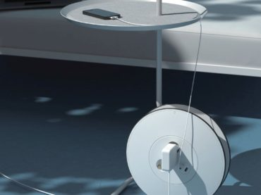 A SIDE TABLE WITH AN EXTENSION CORD TO PLUG IN ALL YOUR VALUABLES